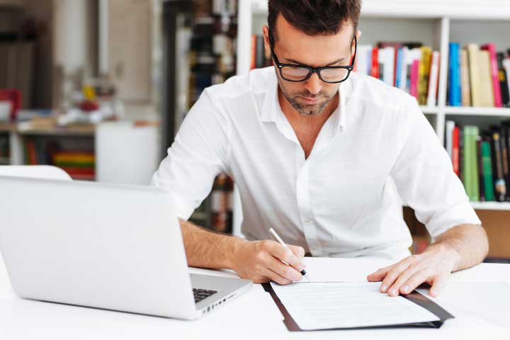 man with glasses writing on pdf paper next to his laptop